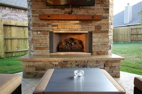 covered patio with outdoor kitchen and fireplace