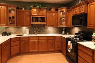 oak kitchen cabinets with granite countertops and black