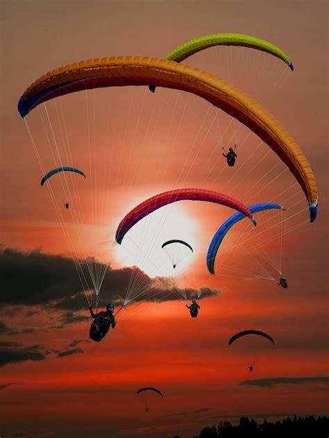 people riding parachutes  sunset  stock photo