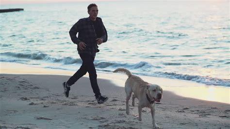 cute young female running   husky dogs   beach
