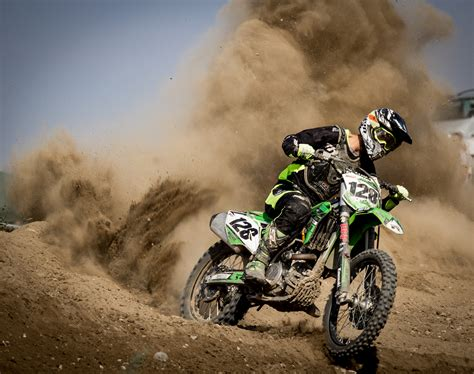 motocross biking rider riding green motocross dirt bike free stock photo
