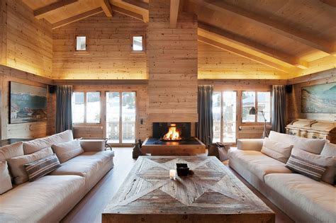 living room with fireplace in the middle and cozy chalet located in gstaad keribrownhomes