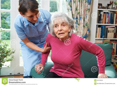 carer helping senior out of chair stock photo