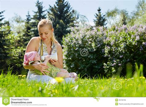 Mother Feeds Baby With Milk From Bottle Royalty Free Stock