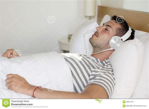 Young Man Sleeping In Bed Listening Music Stock Image