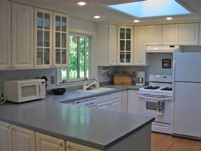 Grey Corian Countertops by Light Grey Corian Counters With White Cabinets Kitchen