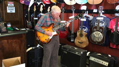 arigen gar   butiken och plockar upp en gitarr det