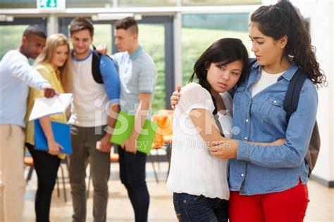friend comforting victim  bullying  school stock