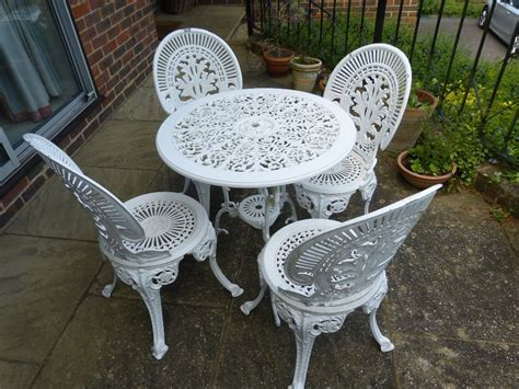 white cast iron garden furniture set table and 4 chairs
