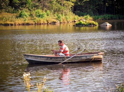 Rowboat Riddle by A Fishing Out Of A Row Boat Stock Photo