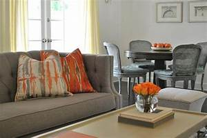 gray and orange living room features a gray tufted high With gray and orange living room
