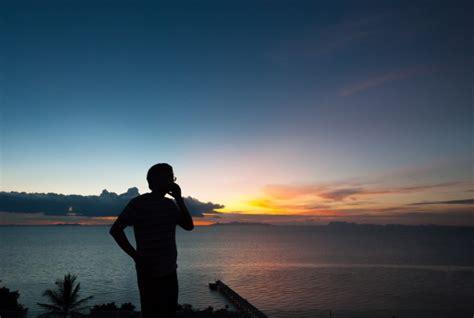 silhouette man talking  phone  sunset view photo