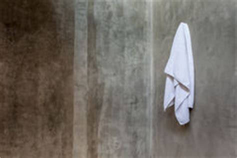 towel draping hanging white towel draped on exposed concrete wall in the