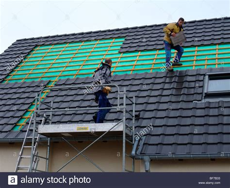 workers removing roof tiles to install photovoltaic solar