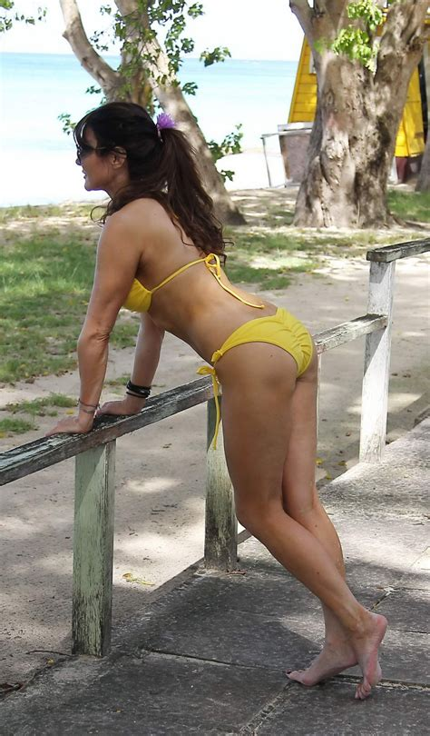 Lizzie Cundy showing off her curvy body in a yellow bikini at the beach in Barba - Pichunter