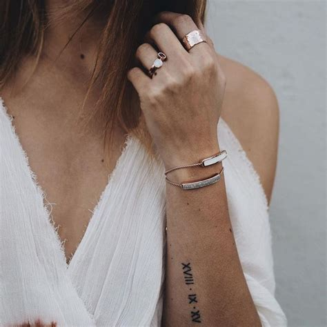 small arm tattoo roman numerals wedding date rose gold