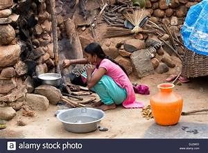 Indian teenage girl cooking rice on an open fire in a ...