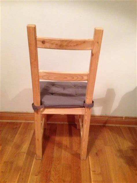 two wooden dining chairs with grey seat cushions for sale