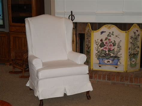 cozy white wingback chair slipcover and fireplace mantle