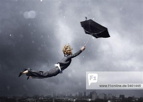 frau wird von einem regenschirm weggeblasen lirm