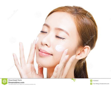 Attractive Young Woman Applying Cream On Her Face Stock