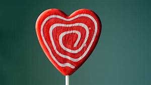 Heart shaped candy lollipop with red and white swirls ...