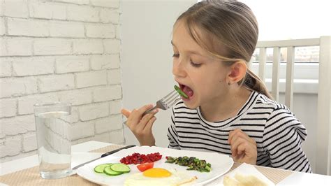 Child Praying Before Eating Breakfast In Kitchen, Girl