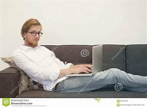 Young Man Sitting On Couch With Laptop Stock Photo - Image ...
