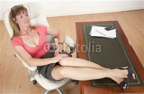 """Mid aged secretary sitting with feet on her desk"" Stock"