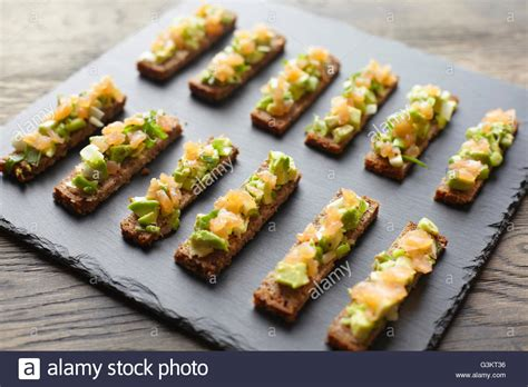 rye bread canapes guacamole smoked salmon and rye bread canapes stock photo