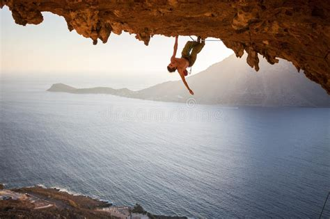 Male Rock Climber Hanging With One Hand While Climbing