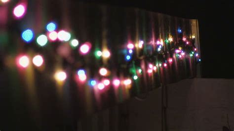 christmas lights draped across a home becomes out of focus