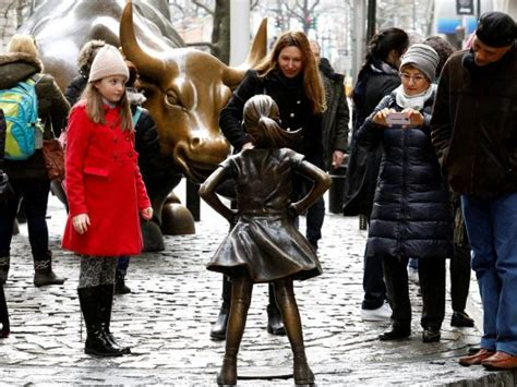 young girl stares  wall streets charging bull