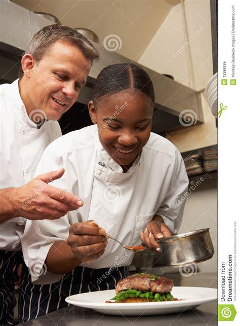 chef instruisant le stagiaire dans la cuisine de restaurant images libres de droits image