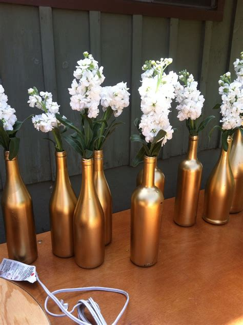 metallic gold spray painted winebottles w white flowers