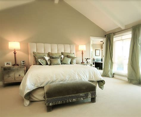 sage green accent wall behind the all white bed with