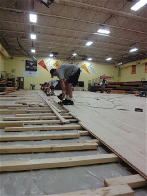 tornado damage  replacing  high school gym floor