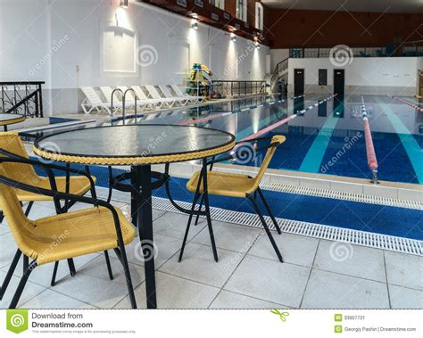 table and chairs near swimming pool stock image image