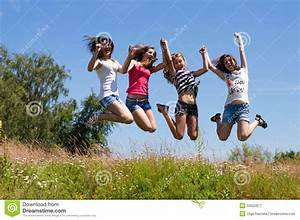 Four Happy Teen Girls Friends Jumping High Against Blue ...