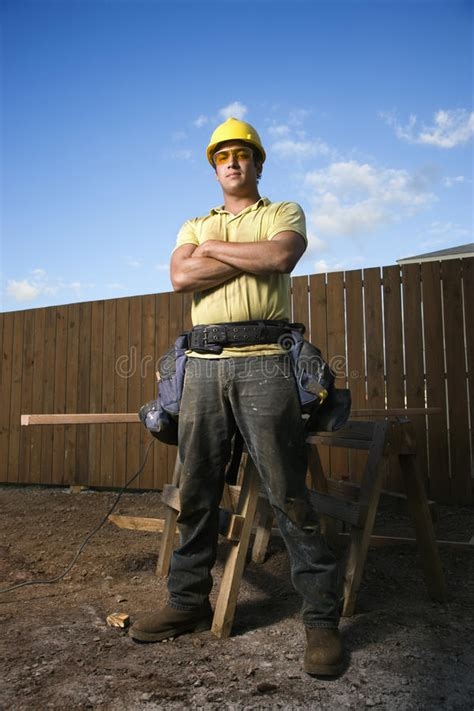 male construction worker stands  folded arms stock