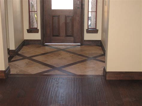 tile wood floors together setting the entryway different from the rest of the floor but still tying them together for