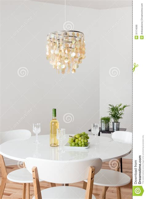 room with decorative chandelier and white table