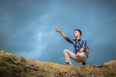 Young Man Top The Mountain Pointing Something