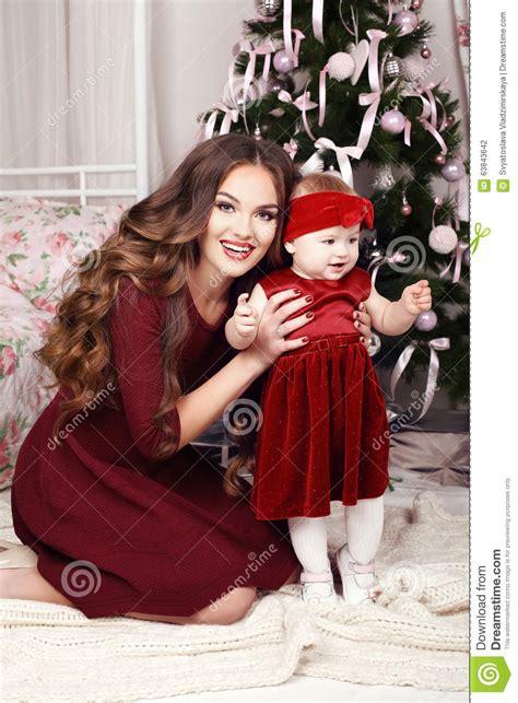 Holiday Photo Of Beautiful Family Posing Beside Christmas
