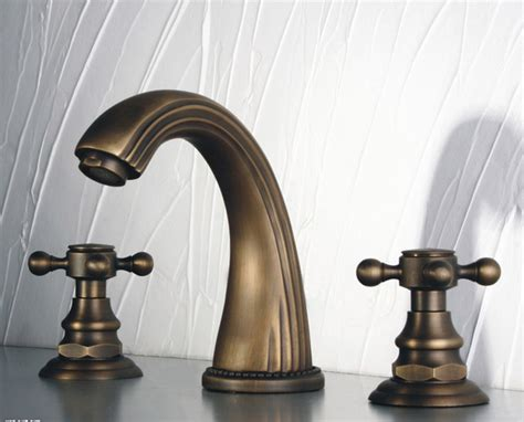antique brass widespread bathroom faucet with cross