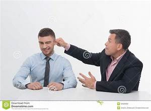 Senior Manager Chief Pulling His Employee Ear Stock Photo