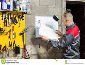 Mechanic Worker Studying His Instructions Stock Photo