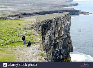 Tourists at steep cliff beside Dun Aengus prehistoric ...