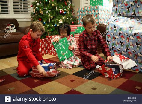 three children opening gifts on christmas day stock photo
