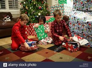 Three children opening gifts on Christmas day Stock Photo ...